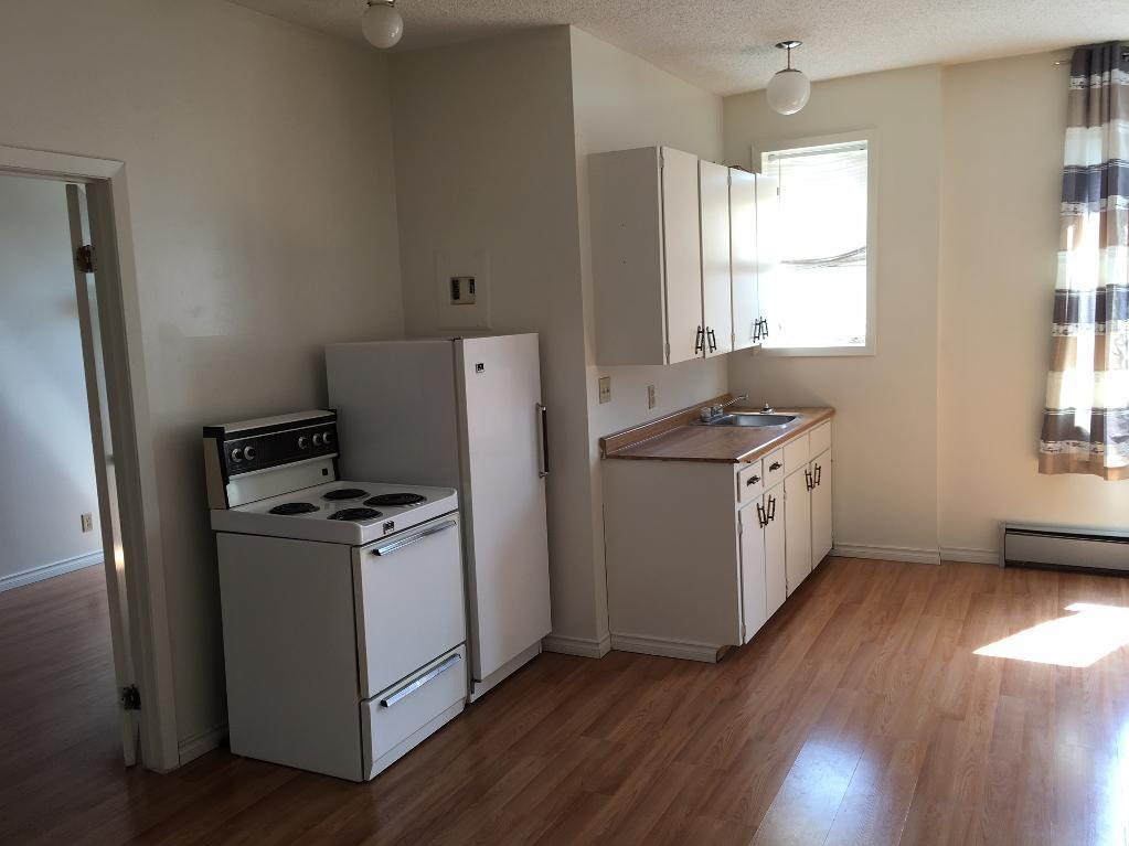 Apartment for rent at 1503 Victoria Ave, Regina, SK. This is the kitchen with natural light, ceiling fan, hardwood floor, oven, radiator and refrigerator.