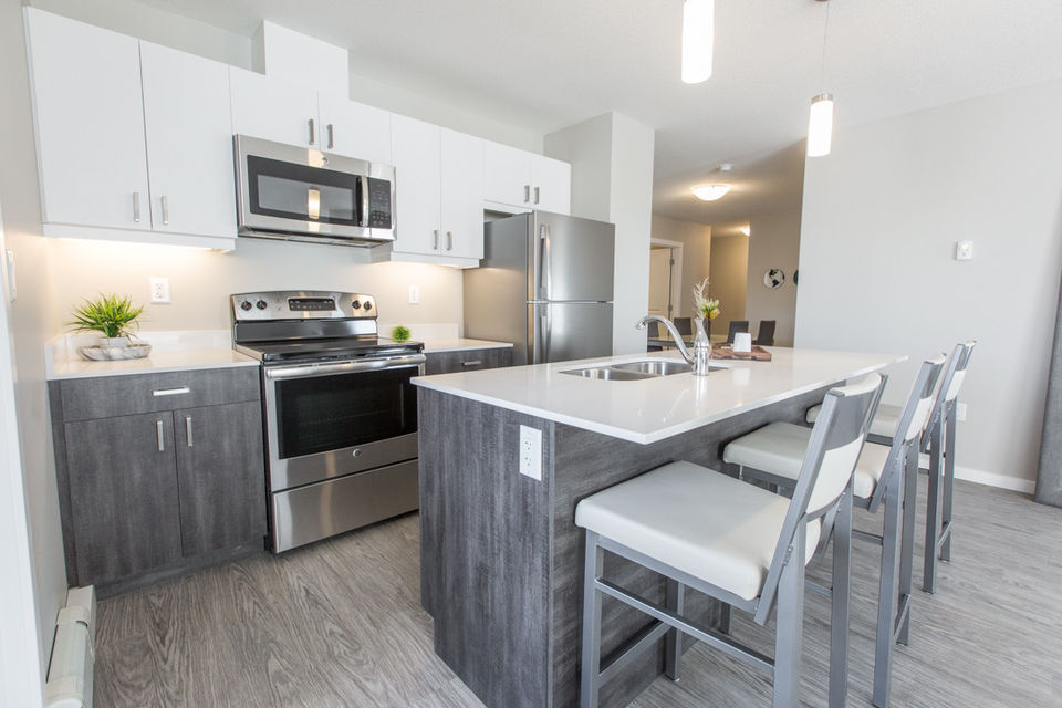 Apartment for rent at 4830 Gordon Rd, Richardson, SK. This is the kitchen with hardwood floor, kitchen island, stainless steel and kitchen bar.