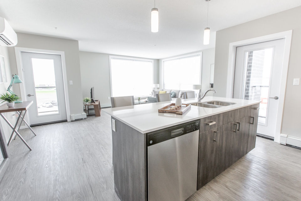 Apartment for rent at 4830 Gordon Rd, Richardson, SK. This is the kitchen with hardwood floor, kitchen island, stainless steel and natural light.