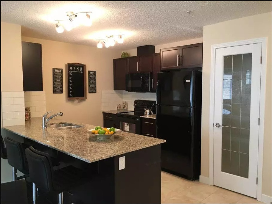 Apartment for rent at 4 & 6 Augustine Crescent, Sherwood Park, AB. This is the kitchen with tile floor, kitchen island and kitchen bar.