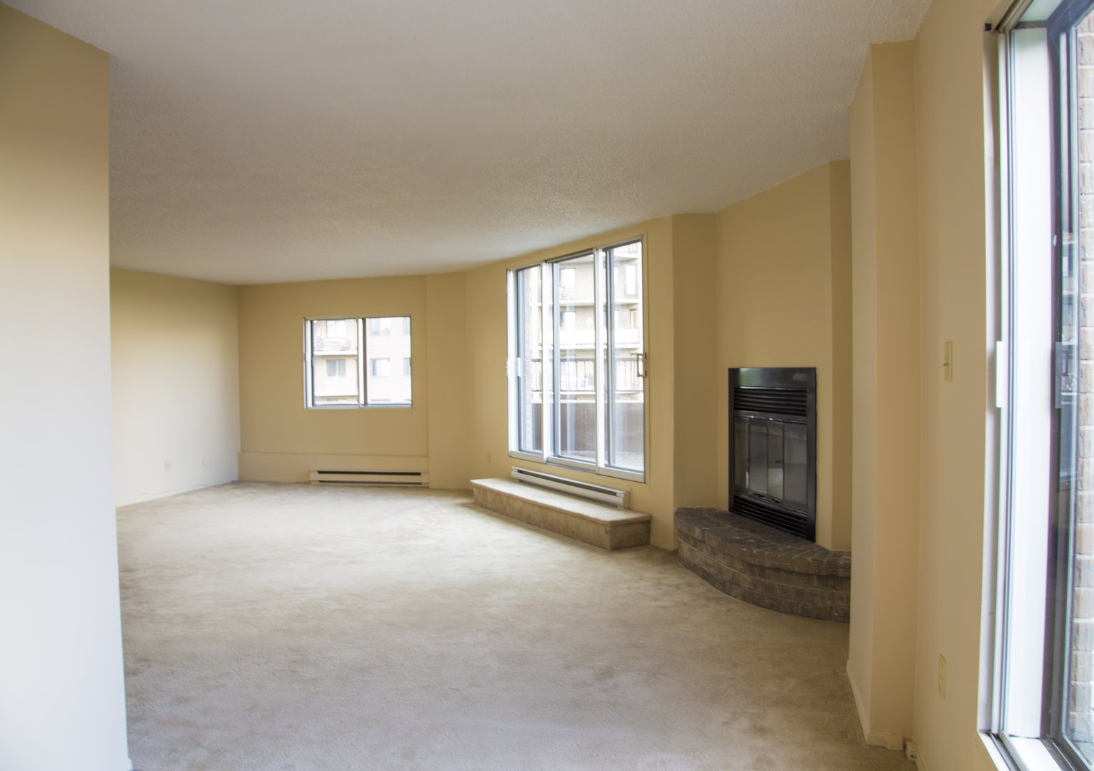 High-Rise Apartment for rent at 50 Quintin, suite 111, Ville Saint-Laurent, QC. This is the empty room with natural light, fireplace and carpet.