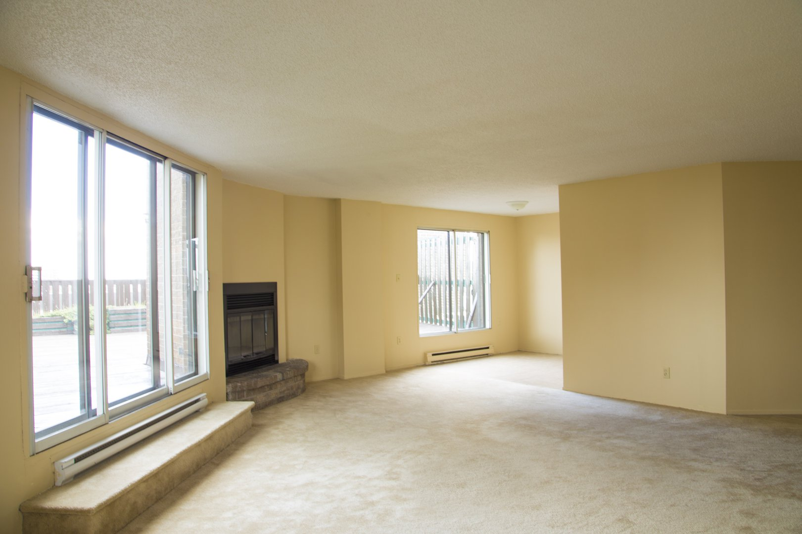 High-Rise Apartment for rent at 50 Quintin, suite 111, Ville Saint-Laurent, QC. This is the empty room with carpet, fireplace and natural light.