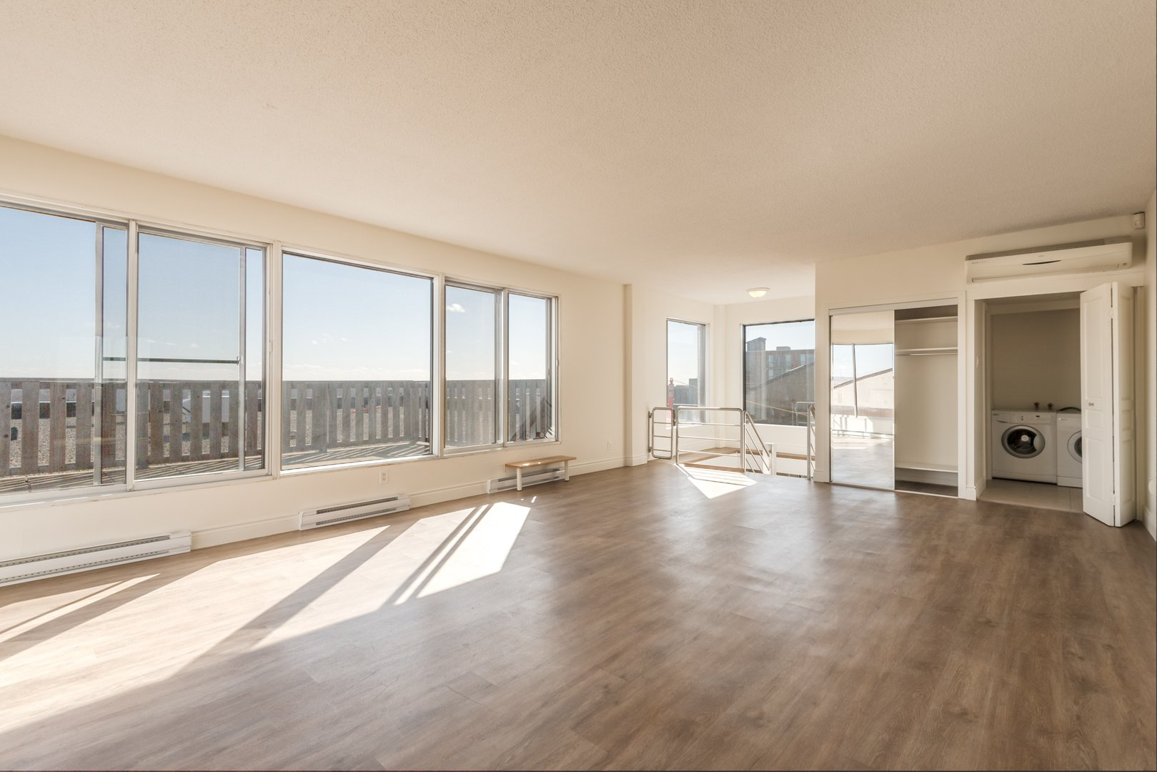 High-Rise Apartment for rent at 50 Quintin, suite 111, Ville Saint-Laurent, QC. This is the empty room with hardwood floor and natural light.
