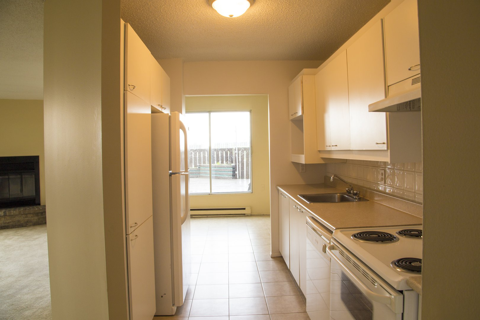 High-Rise Apartment for rent at 50 Quintin, suite 111, Ville Saint-Laurent, QC. This is the kitchen with tile floor, carpet, fireplace and natural light.