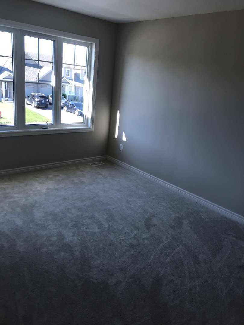 Apartment for rent at 285 Silverwood Ave, Welland, ON. This is the empty room with natural light and carpet.