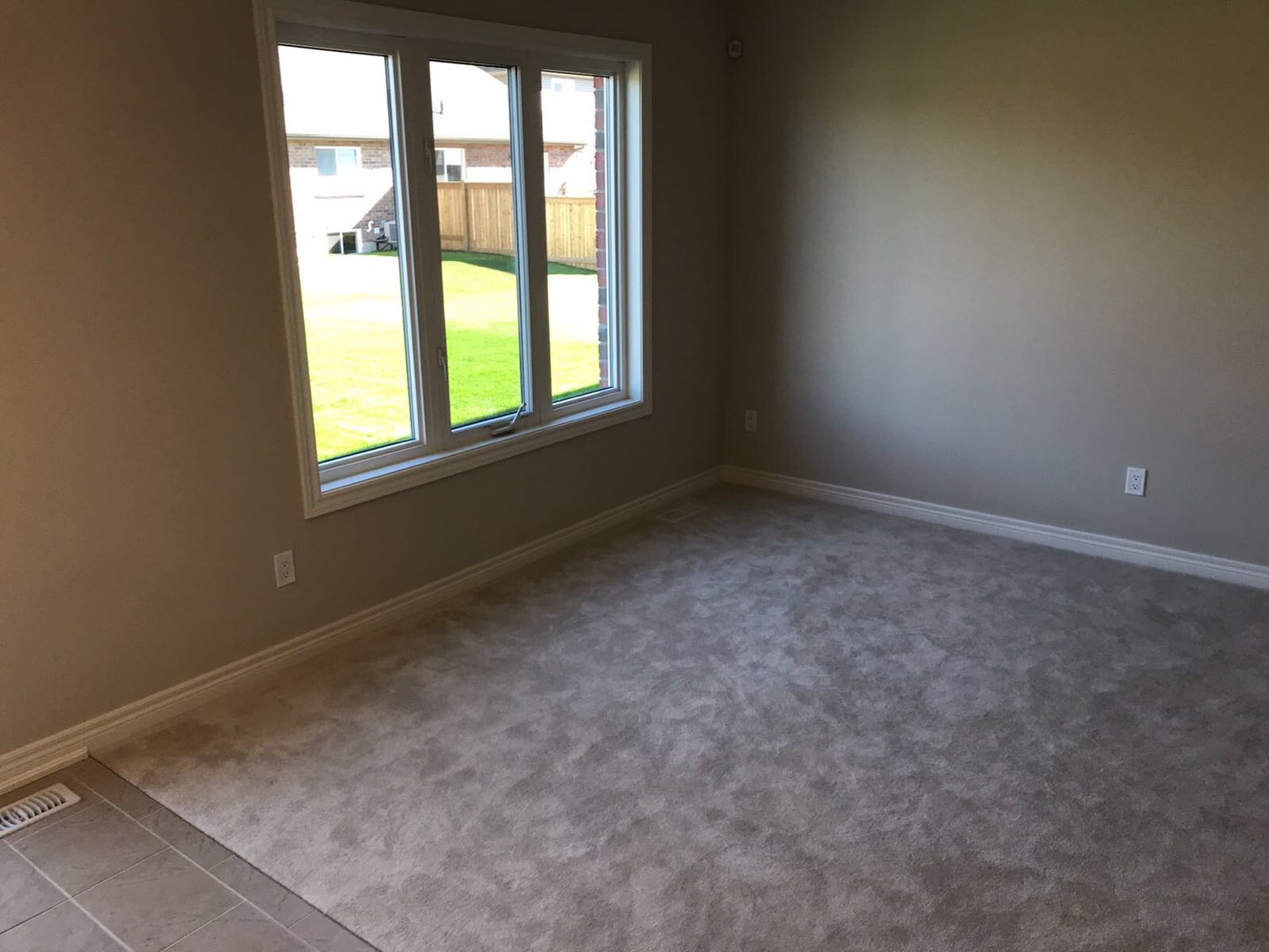 Apartment for rent at 285 Silverwood Ave, Welland, ON. This is the empty room with tile floor, natural light and carpet.