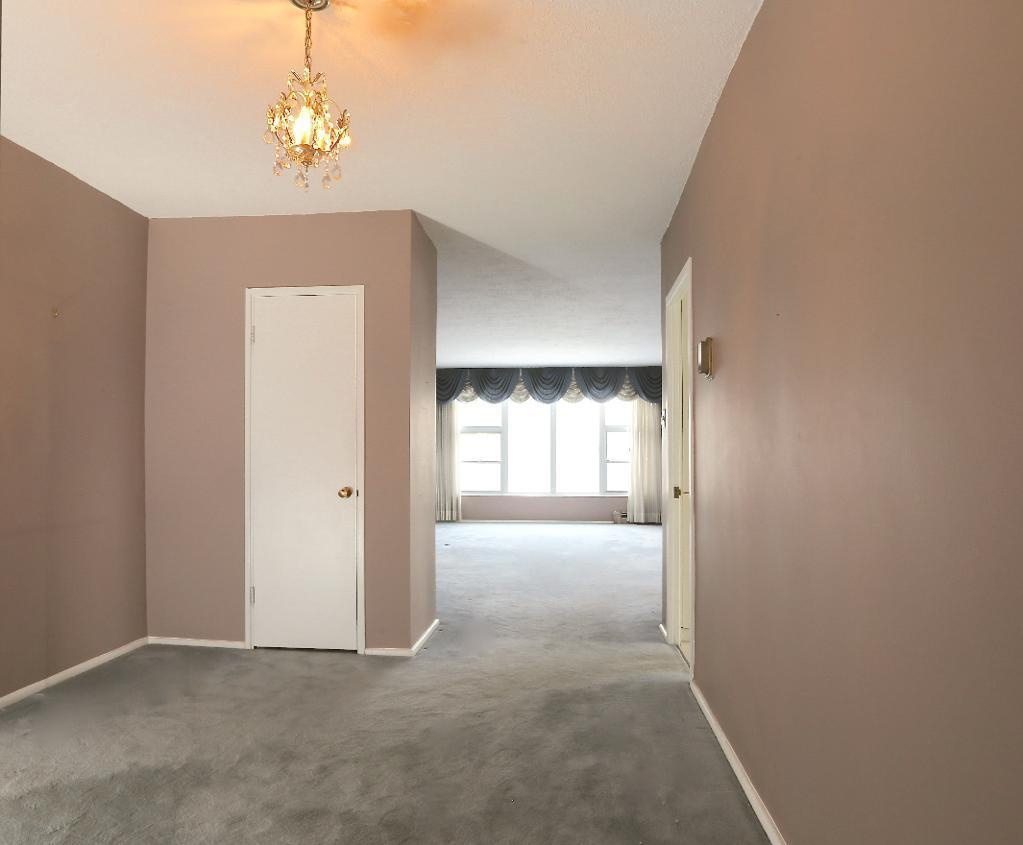 Apartment for rent at 2250 Portage Avenue, Winnipeg, MB. This is the corridor with carpet, natural light and notable chandelier.