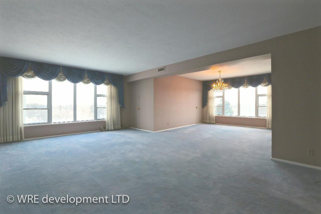 Apartment for rent at 2250 Portage Avenue, Winnipeg, MB. This is the empty room with carpet, natural light and notable chandelier.