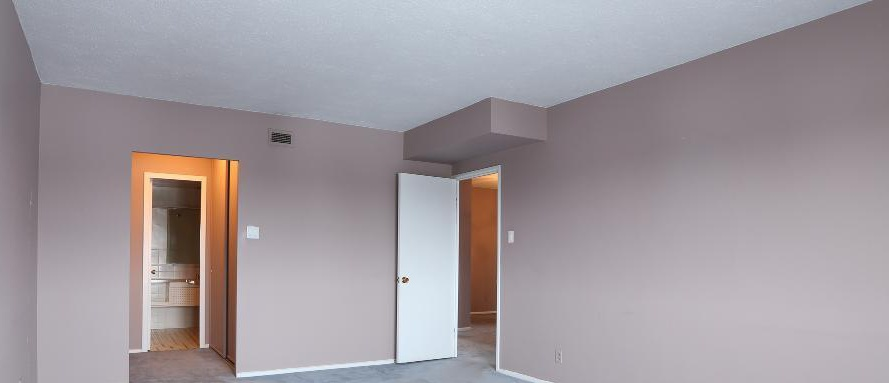 Apartment for rent at 2250 Portage Avenue, Winnipeg, MB. This is the empty room with carpet and vaulted ceiling.