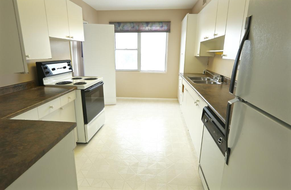 Apartment for rent at 2250 Portage Avenue, Winnipeg, MB. This is the kitchen with natural light, tile floor, oven and refrigerator.