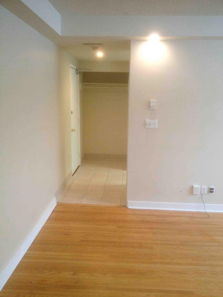 Apartment for rent at 205 St Anthony Avenue, Winnipeg, MB. This is the corridor with tile floor and hardwood floor.