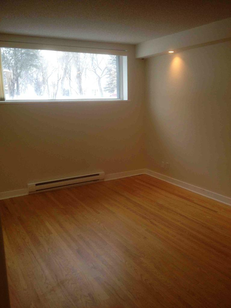 Apartment for rent at 205 St Anthony Avenue, Winnipeg, MB. This is the empty room with natural light and hardwood floor.