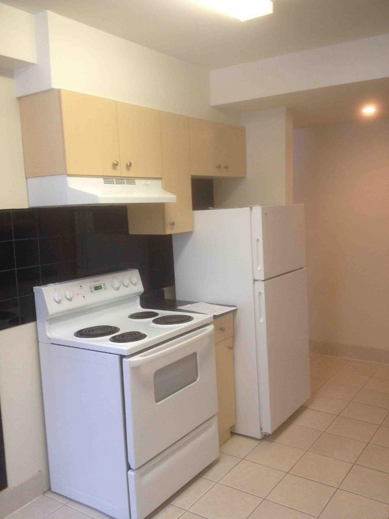 Apartment for rent at 205 St Anthony Avenue, Winnipeg, MB. This is the kitchen with tile floor, oven and refrigerator.